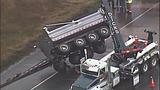 Overturned dump truck spills dirt across highway - (1/18)