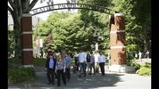 People walk through an arched entrance at Seattle Pacific University in Seattle on their way to a prayer service Friday, June 6, 2014, the day after a fatal shooting at the university. (AP Photo/Ted S. Warren)