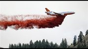 A DC-10 air tanker drops fire retardant over a wildfire Saturday, July 19, 2014, near Carlton, Wash. A wind-driven, lightning-caused wildfire racing through rural north-central Washington destroyed about 100 homes Thursday and Friday, leaving behind solitary brick chimneys and burned-out automobiles as it blackened hundreds of square miles in the scenic Methow Valley northeast of Seattle. (AP Photo/Elaine Thompson)