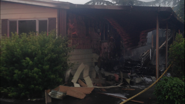 Auburn fire officials said a neighbor helped an 89-year-old woman out of a burning mobile home early Thursday morning.