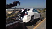 Damaged car being towed after crash with the semi.