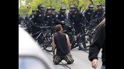 A protester kneels before police officers as he takes part in a May Day anti-capitalism march, Friday, May 1, 2015 in Seattle. (AP Photo/Ted S. Warren)