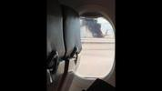 In this photo provided by David Somers and taken from the view of a plane window, smoke billows out from a plane that caught fire at McCarren International Airport, Tuesday, Sept. 8, 2015, in Las Vegas. An engine on the British Airways plane caught fire before takeoff, forcing passengers to escape on emergency slides. (David Somers via AP)