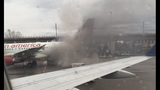 Baggage cart catches fire near plane at Sea-Tac Airport_8453671