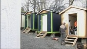 Volunteers put the finishing touches on small houses with the kind of basic amenities you don't see in Seattle homeless camps.