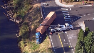 Semi-truck hanging on embankment near Duwamish River