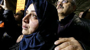 Emtisal Bazara cries as she and her husband, Ahmad Bazara, both recent Syrian immigrants, look on at a rally to oppose President Donald Trump's executive order in downtown Seattle on Sunday. (AP Photo/Elaine Thompson)