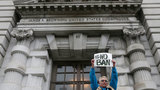 FILE - In this Feb. 7, 2017, file photo, Karen Shore holds up a sign outside of the 9th U.S. Circuit Court of Appeals in San Francisco, Calif. (AP Photo/Jeff Chiu, File)