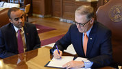 Inslee signing an executive order on immigration. Photo via Office of Governor Jay Inslee.