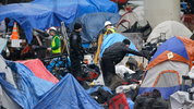 A Seattle Police officer, center, looks on as workers prepare to clear belongings and shelter materials from a large homeless encampment known as