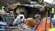 FILE: Workers dismantle a shelter at a large homeless encampment known as