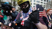 A supporter of President Donald Trump makes a hand symbol as he takes part in a May Day protest, Monday, May 1, 2017, in Seattle. (AP Photo/Ted S. Warren)