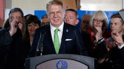 Seattle Mayor Ed Murray briefly smiles as supporters applauds his entrance before saying that he is dropping his re-election bid for a second term, Tuesday, May 9, 2017, in Seattle. (AP Photo/Elaine Thompson)