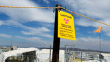 """FILE--In this July 9, 2014, file photo, a sign warns of radioactivity near a wind direction flag indicator at the """"C"""" tank farm on the Hanford Nuclear Reservation near Richland, Wash. (AP Photo/Ted S. Warren, file)"""