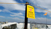 FILE--In this July 9, 2014, file photo, a sign warns of radioactivity near a wind direction flag indicator at the