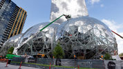 FILE - In this April 27, 2017 file photo, construction continues on three large, glass-covered domes as part of an expansion of the Amazon.com campus in downtown Seattle. (AP Photo/Elaine Thompson)