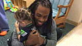 """Richard Sherman visits Ellie, a 4-year-old patient at Mary Bridge Children's Hospital in Tacoma. Her favorite doll is """"Shermie."""" (Courtesy of Megan Carter)"""