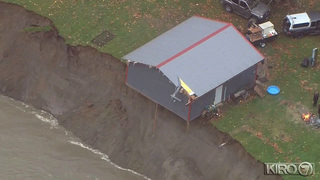 Shed dangling over Skagit River bank that apparently eroded during flooding