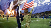 U.S. Army Chief Warrant Officer 3 Jeremy W. Bruffett, right, carries a U.S. flag as he runs with the Seattle Seahawks flag crew before the start of an NFL football game against the Atlanta Falcons, Monday, Nov. 20, 2017.  (AP Photo/Ted S. Warren)