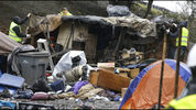 Workers dismantle a shelter at a large homeless encampment known as