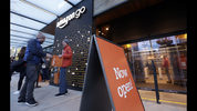 A customer is handed a complimentary shopping bag as he heads into an Amazon Go store, Monday, Jan. 22, 2018, in Seattle. (AP Photo/Elaine Thompson)