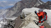 A climber takes a photo of the crater from the rim of Mount St. Helens in 2007. Craig Hill, The News Tribune
