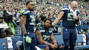 Teammates show their support for Seahawks DE Michael Bennett during a silent protest.
