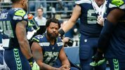 Thomas Rawls #34 of the Seattle Seahawks stands with center Justin Britt #68, right, to join defensive end Michael Bennett #72 on the bench during the national anthem before a game at CenturyLink Field (Photo by Otto Greule Jr /Getty Images)