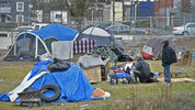 Homeless individuals huddle among their tents and possessions on a vacant lot in the 1000 block of South J Street in Tacoma's Hilltop neighborhood on Tuesday, Feb. 27, 2018. The News Tribune, file photo