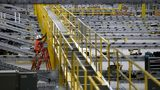 A worker makes repairs to a conveyor belt system that is under construction at a new Amazon fulfillment center on August 10, 2017 in Sacramento, California. (Photo by Justin Sullivan/Getty Images)