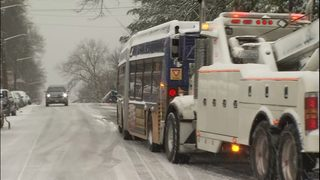 RAW: Metro bus with chains needs push from tow truck
