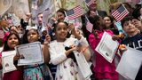 Children wave American flags and hold their certificates of citizenship after becoming U.S. citizens during a citizenship ceremony at The Bronx Zoo, May 5, 2017. (Photo by Drew Angerer/Getty Images).