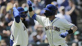 Seattle Mariners' J.P. Crawford, left greets Mitch Haniger after scoring on Haniger's two-run home run on a pitch from Minnesota Twins' Kyle Gibson during the fifth inning of a baseball game, May 19, 2019, in Seattle. (AP Photo/John Froschauer)