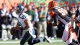 Russell Wilson #3 of the Seattle Seahawks attempts to scramble away from Carlos Dunlap #96 of the Cincinnati Bengals during the second quarter at Paul Brown Stadium on October 11, 2015 in Cincinnati, Ohio. (Photo by John Grieshop/Getty Images)